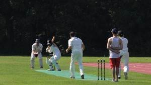 Umpire Bowes in traditional dress, Weston hits to leg and Altmann prepares to run